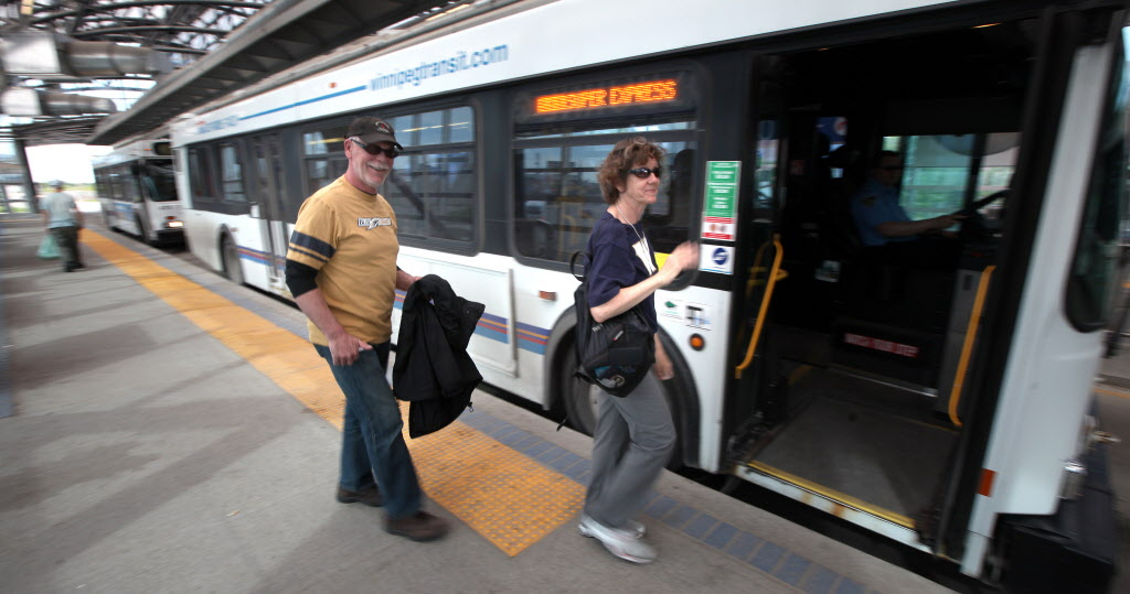 Bombers fans Tom and Randi Donahue board an express bus to Investors Group Field Monday night at Osborne station.