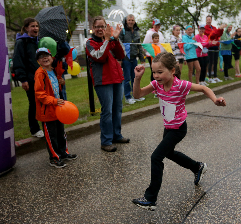 Supported by her brother Zachary, 8, and mother, Kristene, Emma Pauls, 5, wins the Mini Mites race at the Manitoba Marathon at the University of Manitoba, Sunday, June 15, 2014.