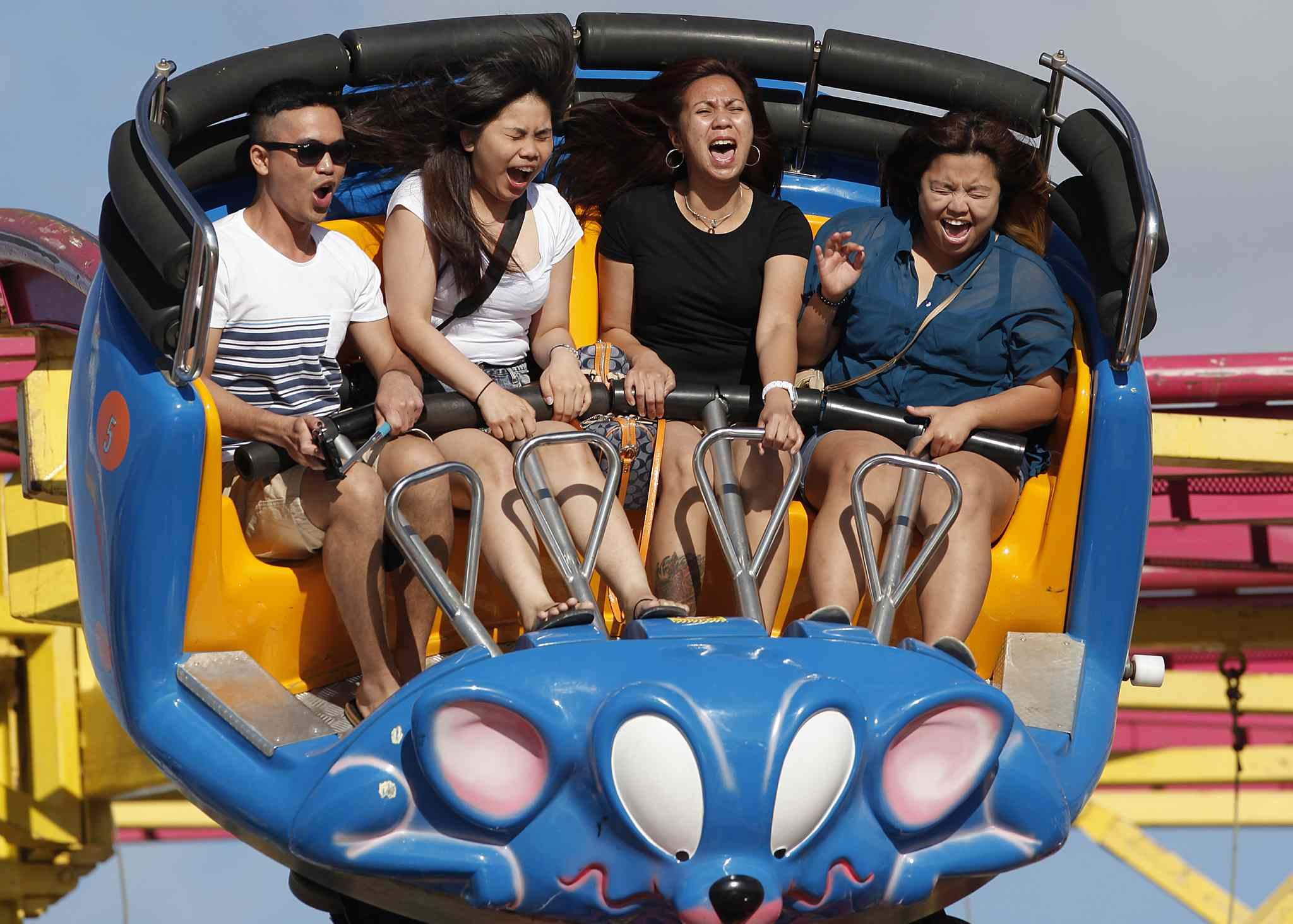 From left, Ace Martin Prieto, Norlyn Brual, Cynthia Berces and Naldine Reyeson take a ride on the Crazy Mouse at The Red River Ex on Tuesday.