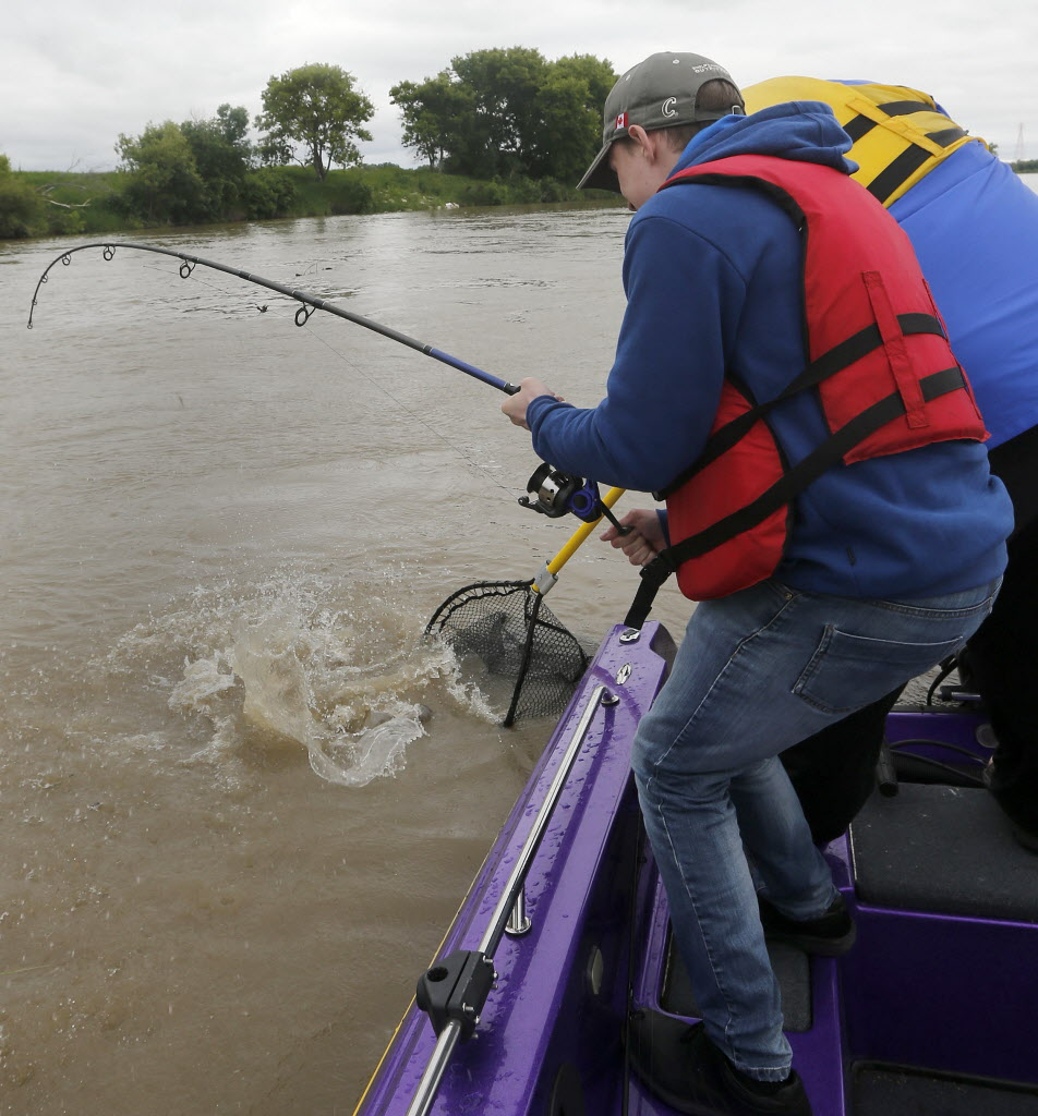 Reporter Oliver Sachgau feels a tug on his line and tries to haul in what he hopes is a big catfish.