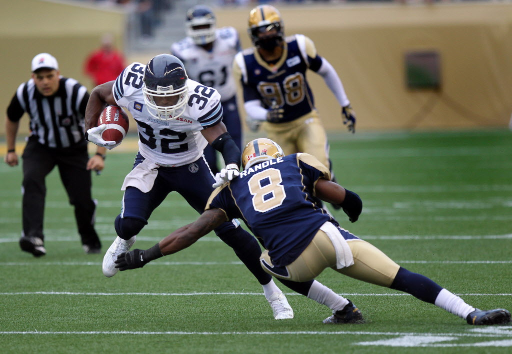 Toronto Argonaut #32 Andre Durie skips over Winnipeg Blue Bomber #8 Chris Randle Thursday at Investors Group Field in Winnipeg. (Phil Hossack / Winnipeg Free Press)
