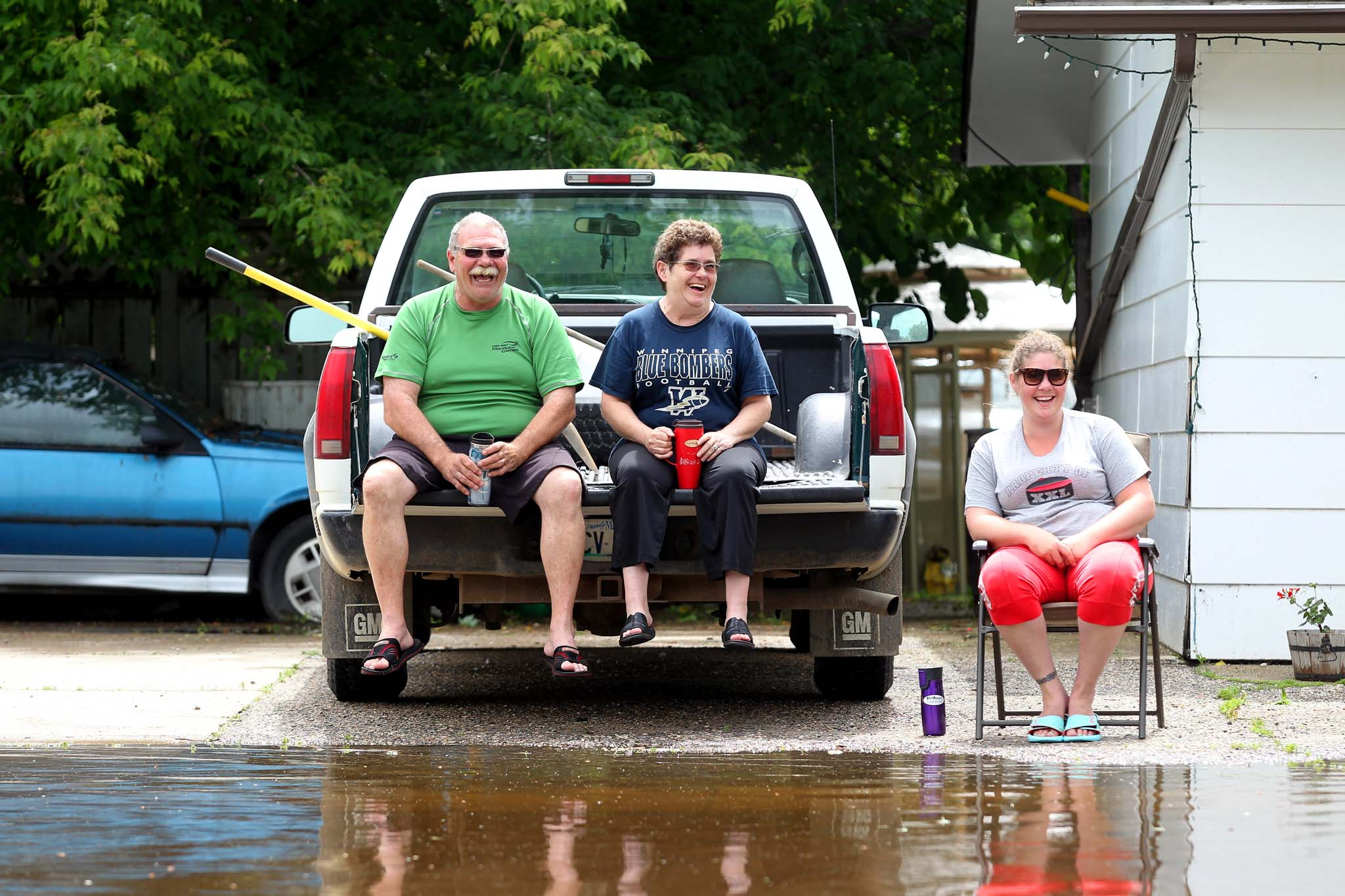 Bill Hayward, his wife Brenda and daughter Carly watch the water from the swollen Gopher Creek slowly rise in front of their home on King Street in Virden on Monday afternoon.