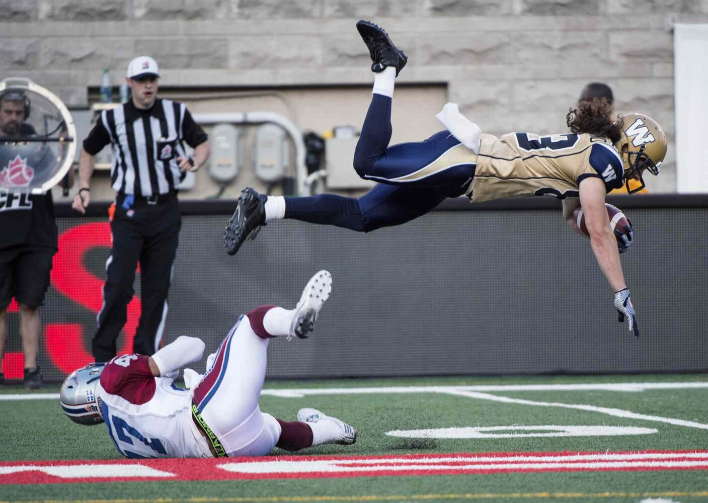 Winnipeg Blue Bombers' wide receiver Julian Feoli-Gudino flies over Montreal Alouettes' defensive back Jamaan Webb during first quarter CFL football action Friday, July 11, 2014 in Montreal.