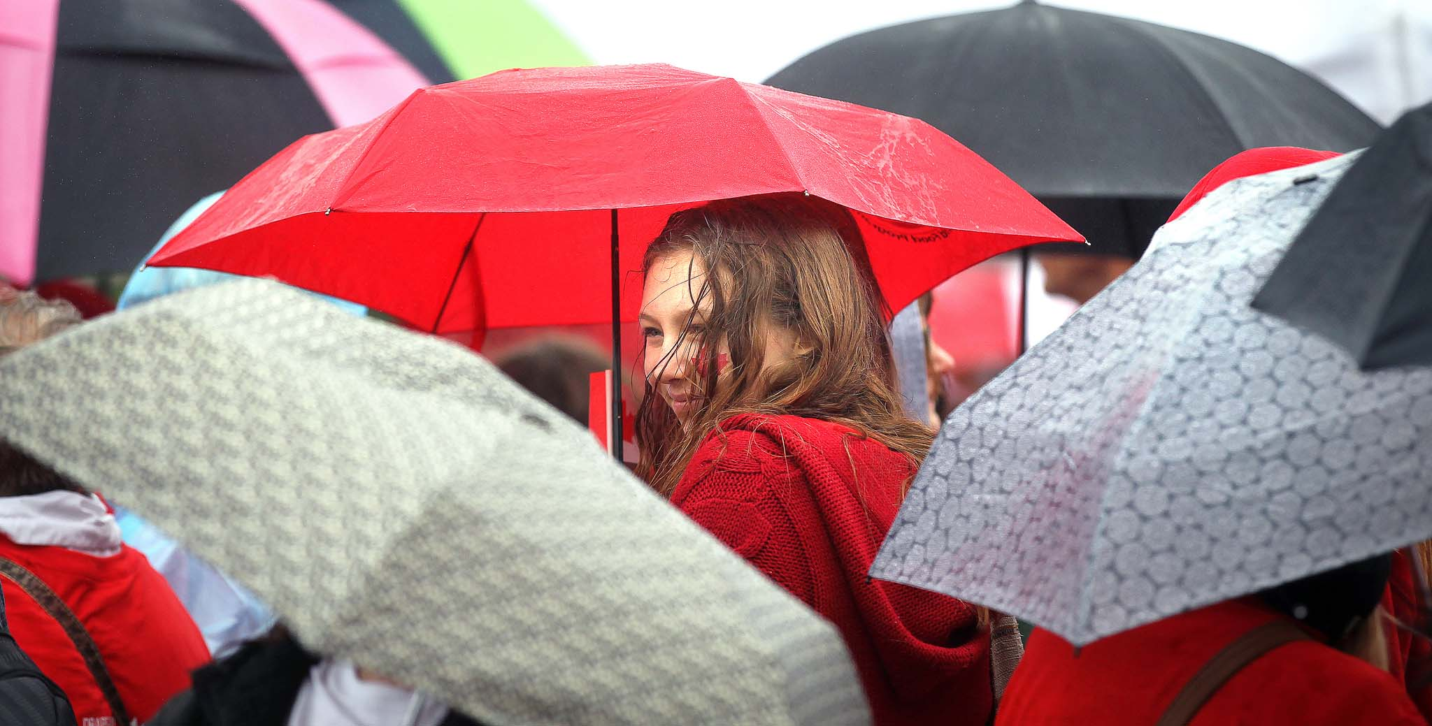 Framed in umbrellas, Elisabeth Kehler waits to participate.