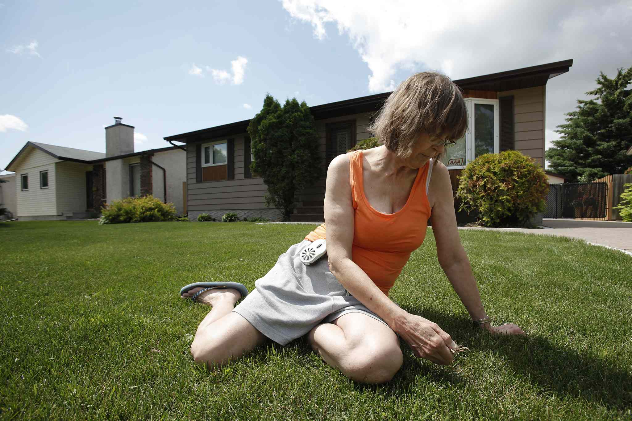 Maples resident Debbie Lynch weeds her lawn while wearing a mosquito deterrent on her hip.