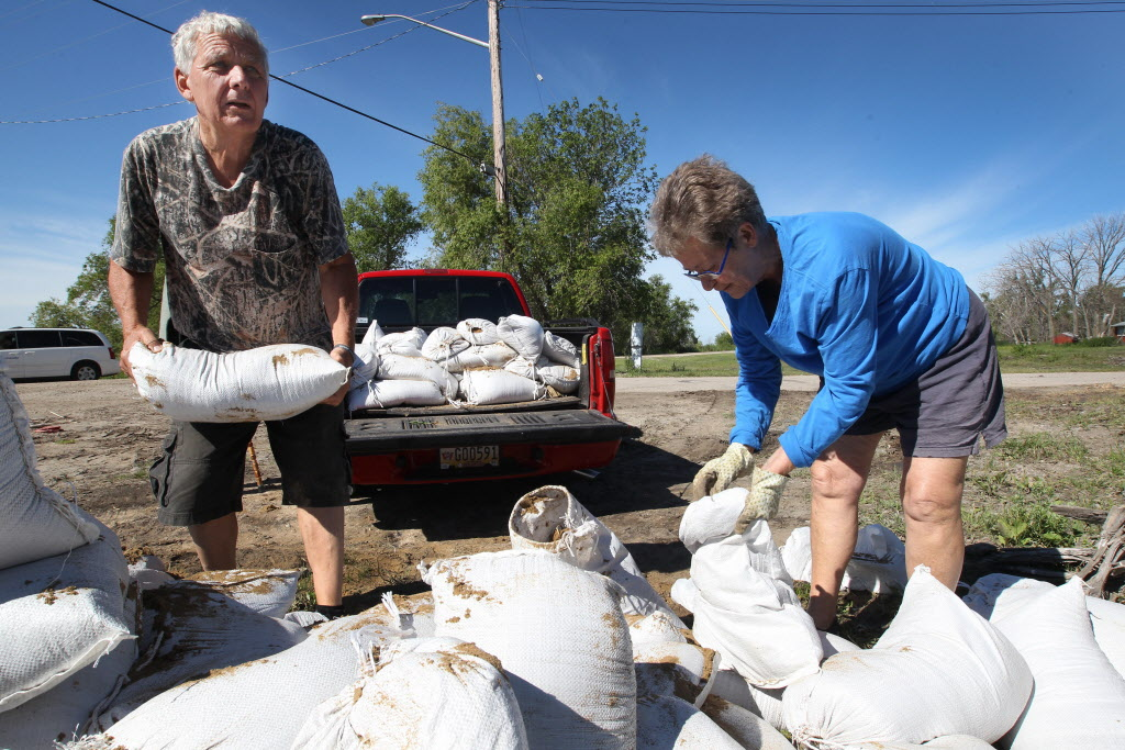 Terry Hutchinson and Betty Granger sling sandbags at East Delta Beach Monday.