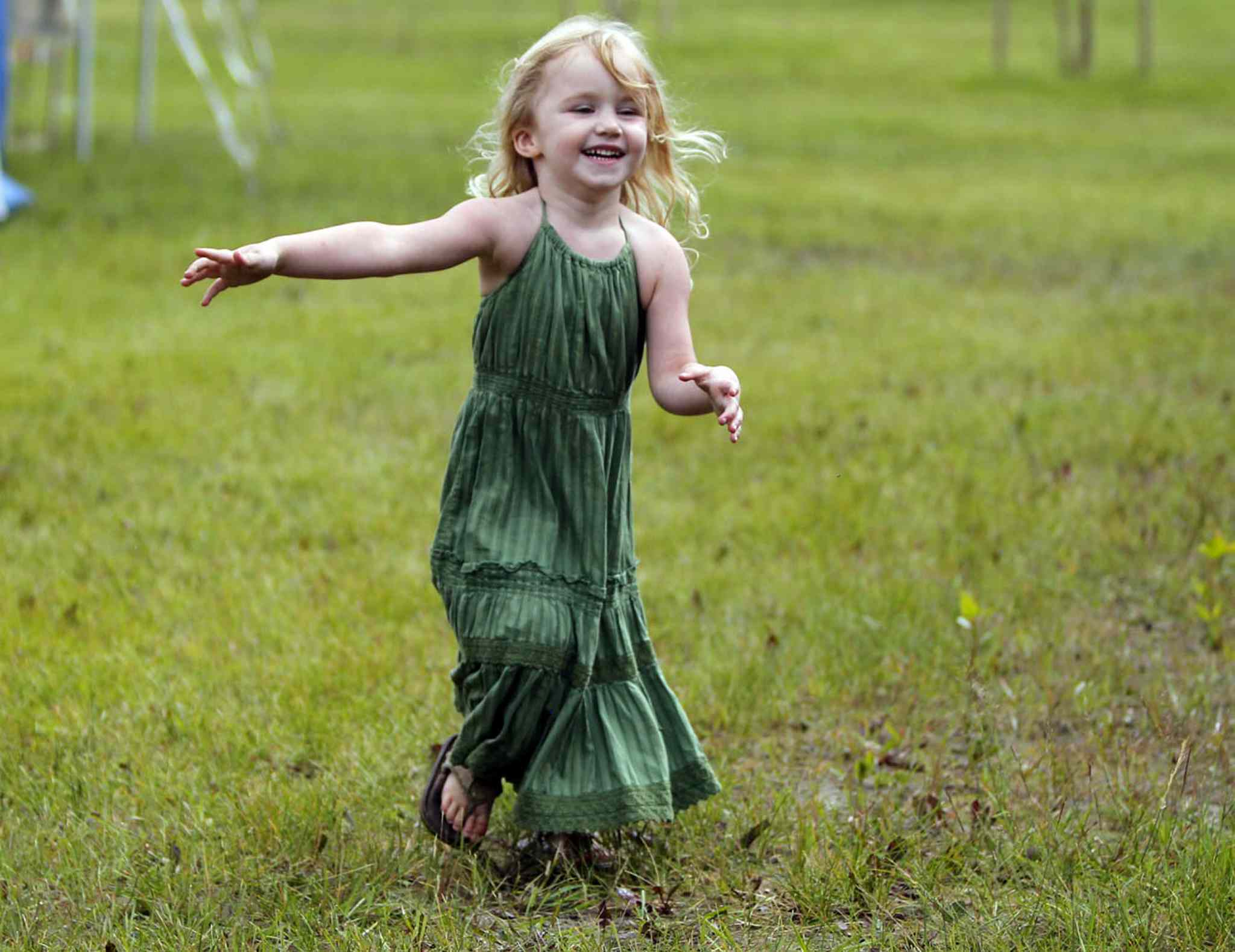 Three-year-old Briar MacDonald runs around as her mom and grandmother set up their craft sale tent at Winnipeg Folk Festival. The popular music festival starts tomorrow.