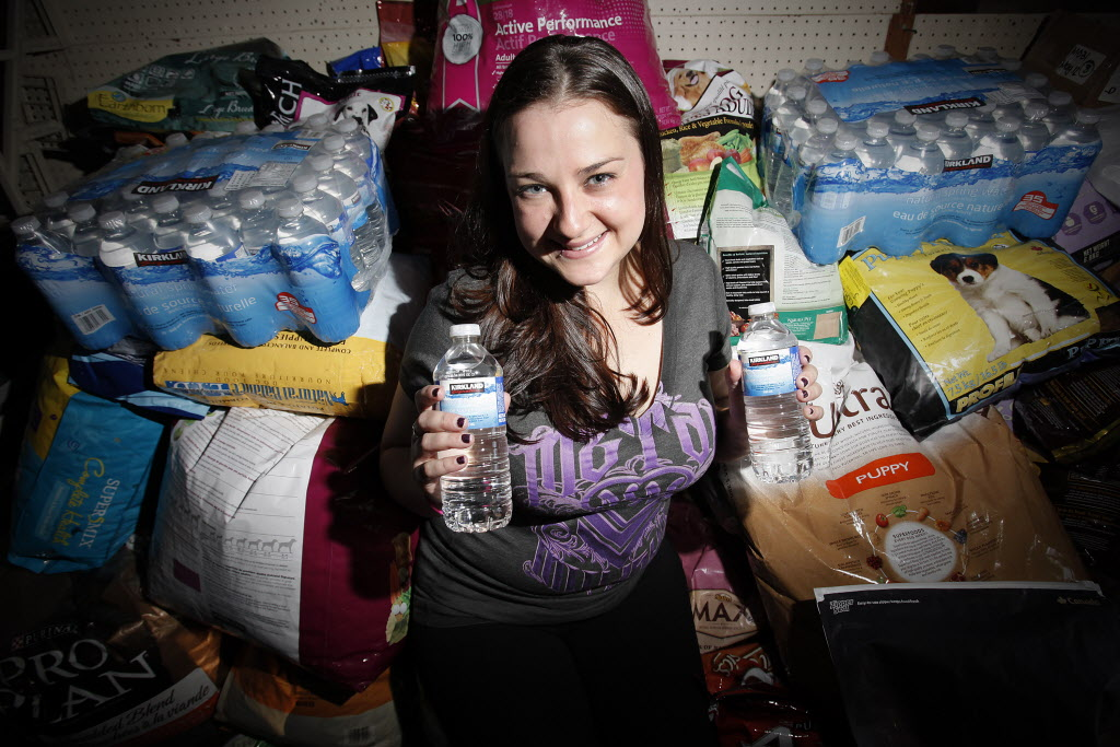 Katie Powell is surrounded by donations of pet food and water to help feed animals left behind because of flooding.