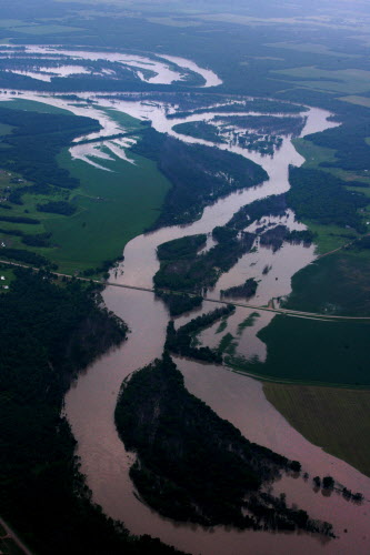 Heavy rains in western Manitoba and Saskatchewan have raised the level of the Assiniboine River causing it to overflow its banks flooding roads and farmers fields.
