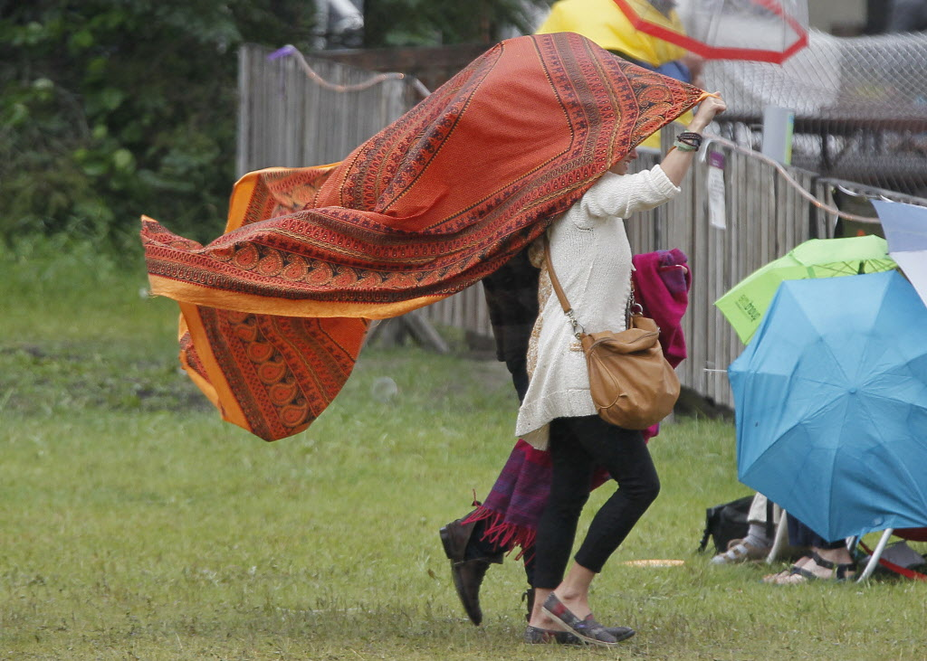 Attendees cover up on a very wet final day of Folk Fest Sunday, July 13, 2014.
