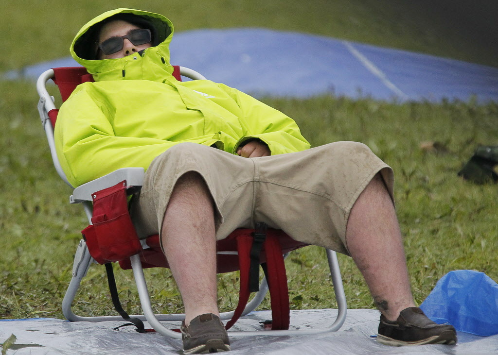 A man kicks back despite the rainy conditions at Folk Fest Sunday, July 13, 2014.