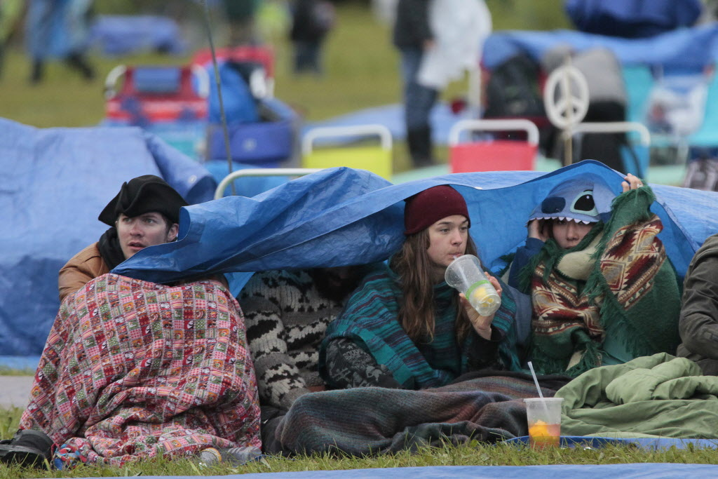 Fans enjoy some drinks under the cover of a tarp on a very wet final day of Folk Fest Sunday, July 13, 2014.