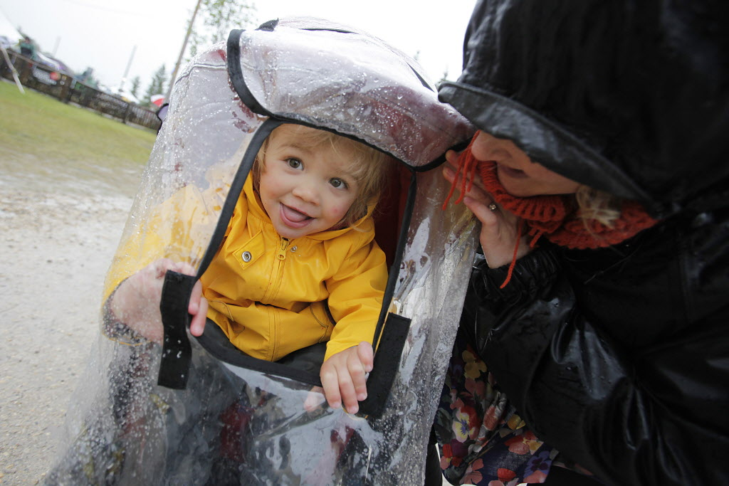Miriam Recksiedler and her mom Jillian check to see if the rain has stopped on a very wet final day of Folk Fest Sunday, July 13, 2014.  (John Woods / Winnipeg Free Press)