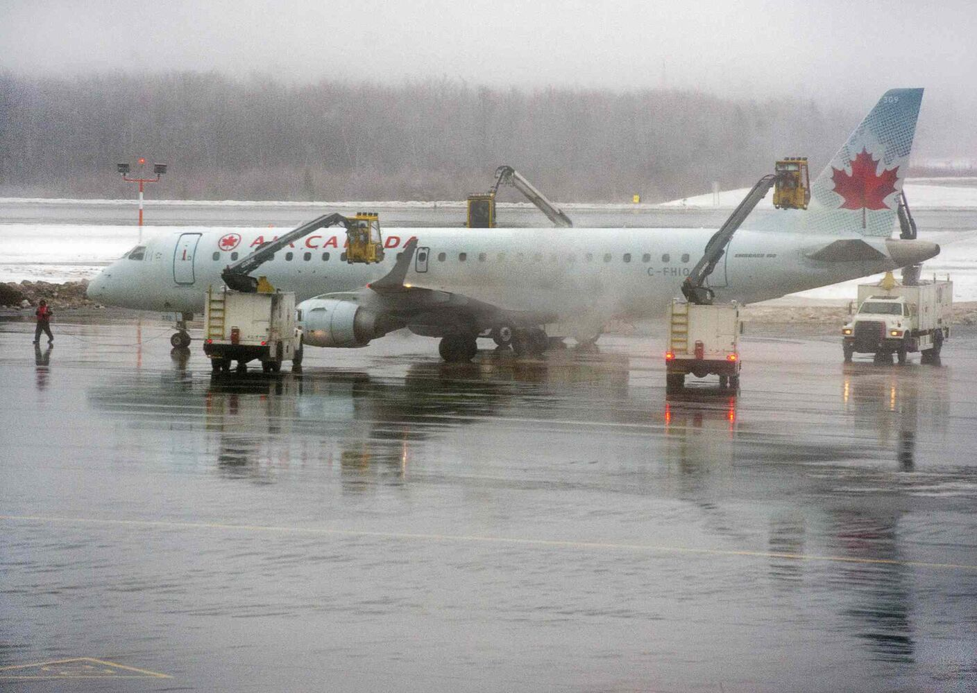 An Air Canada jet is de-iced at Halifax Stanfield International Airport in Halifax on Sunday. Much of Eastern Canada has been affected by the adverse weather, with rain, freezing rain and snow disrupting Christmas travel. (Andrew Vaughan / The Canadian Press)