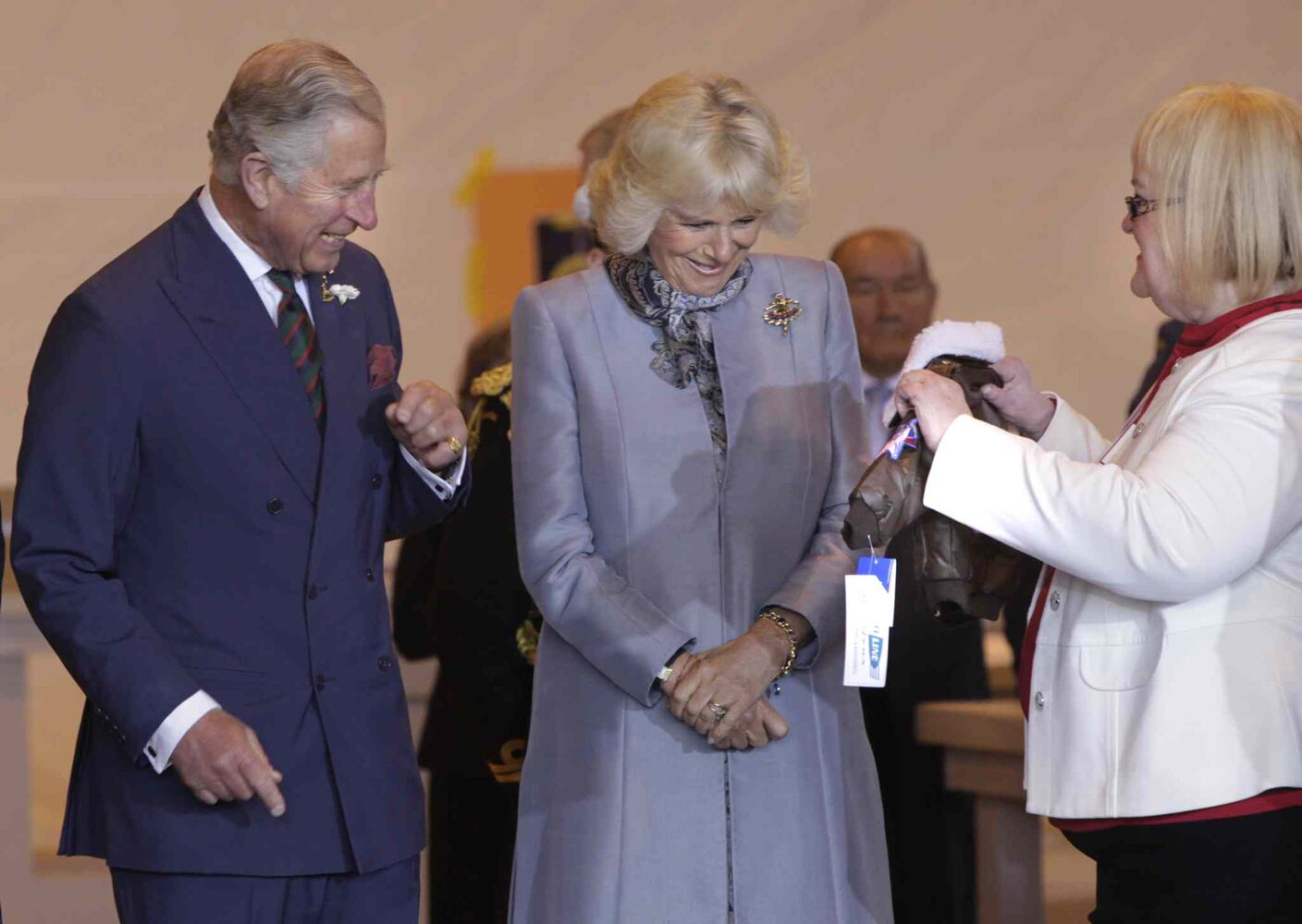 At right, Barb Bowen presents Prince Charles and Camilla, Duchess of Cornwall a flight jacket for Prince George at the ceremony in the Stevenson Hangar Wednesday morning.
