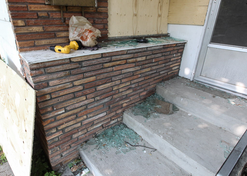 Shattered glass lines the outside stairs of 512 Stella Avenue, the home where Andrew Baryluk died during an armed standoff with the police.  (MIKE DEAL / WINNIPEG FREE PRESS)