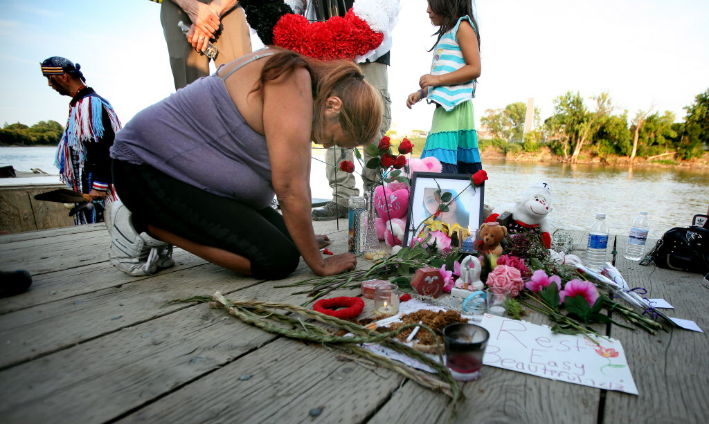 Lana Fontaine, an aunt of Tina Fontaine, weeps at a memorial shrine built on the bank of the Red River where her niece's body was recovered. About a thousand people gathered at the Alexander Docks Tuesday evening to honor Tina and Faron Hall.