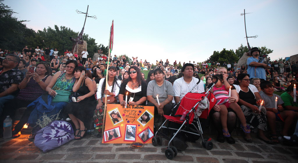 Tina Fontaine (center in black with sunglasses), mother of 15-year-old Tina Fontaine, sits at a rally inside the Oonida Circle at the Forks in Winnipeg Tuesday evening.