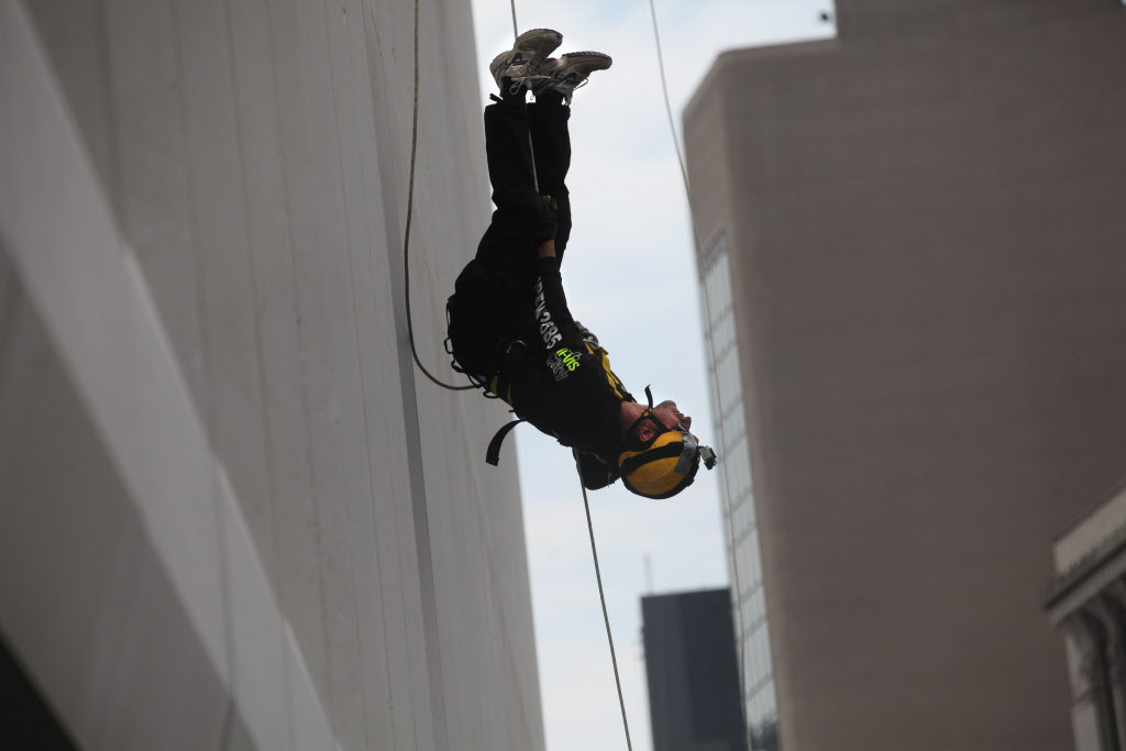 Warren Herntier flips upside down as he nears the bottom of the RBC building after rappelling 200 feet during the annual Easter Seals Drop Zone event.  (Ruth Bonneville / Winnipeg Free Press)
