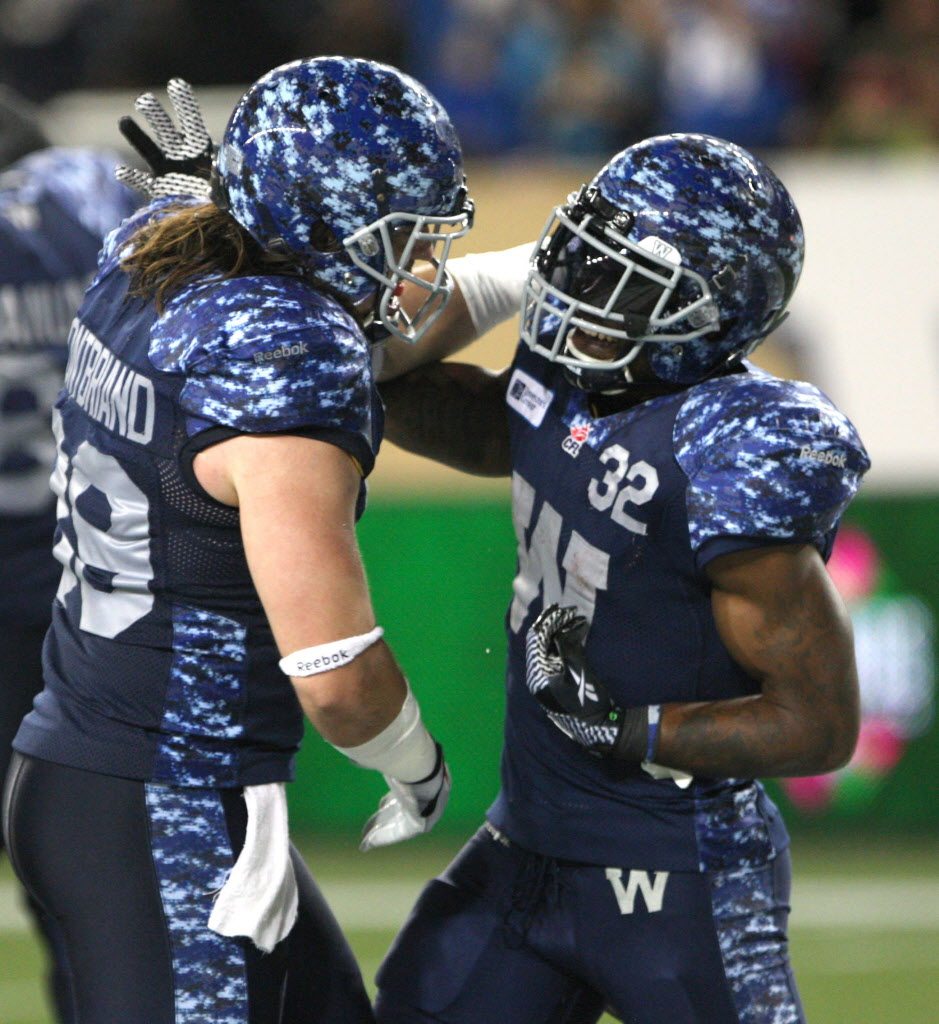 Winnipeg Blue Bombers Nic Grigsby, right, is congratulated by teammate Michel-Pierre Pontbraid after scoring the game-winning touchdown to beat the Montreal Alouettes.