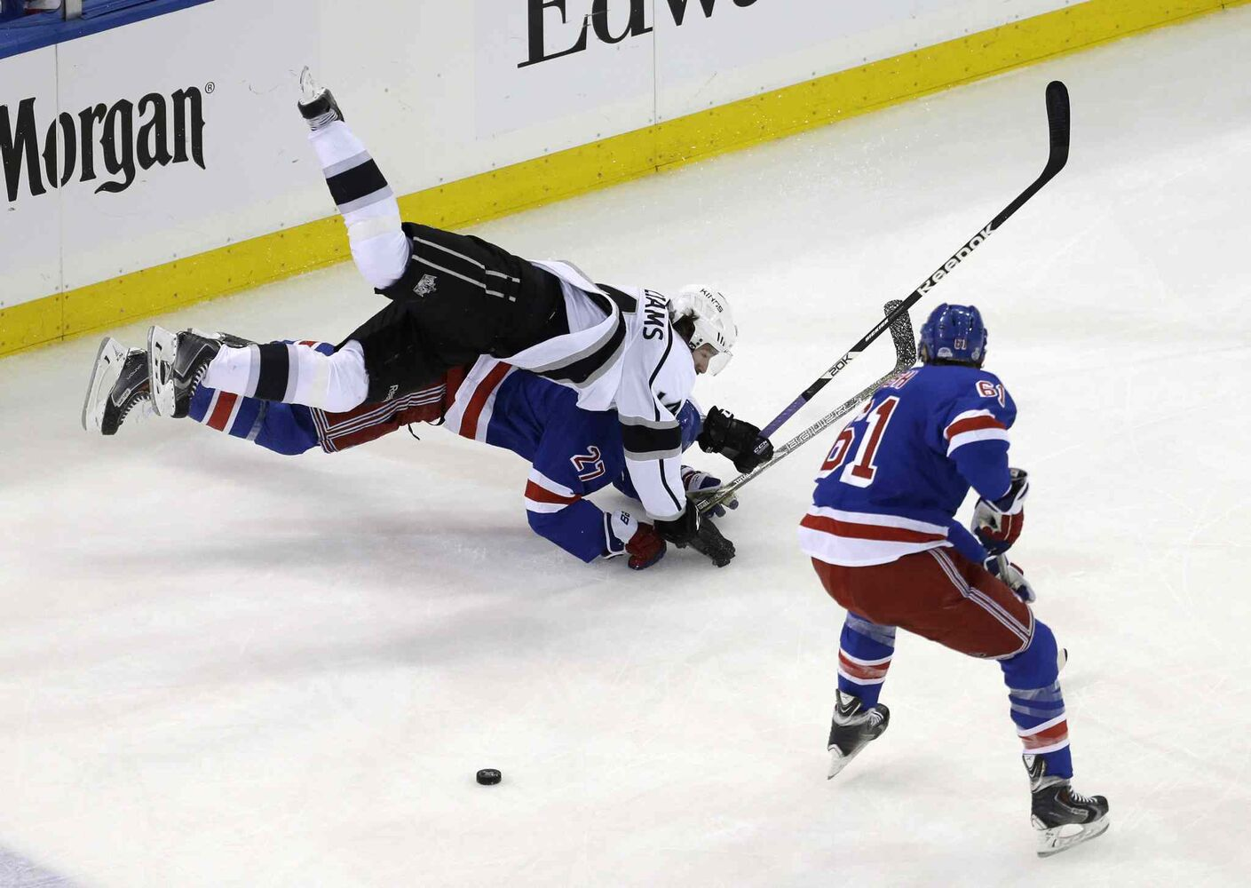 While New York Rangers' left wing Rick Nash (61), right, looks on, Los Angeles Kings' right wing Justin Williams (14), top, gets tangled up with New York Rangers' defenseman Ryan McDonagh (27) in the first period of Wednesday's game.