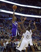 Sacramento Kings guard Ramon Sessions (9) puts up a shot over New Orleans Pelicans guard Jrue Holiday (11) in the first half of an NBA basketball game in New Orleans, Tuesday, Nov. 25, 2014. (AP Photo/Butch Dill)