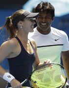 Martina Hingis of Switzerland, left, and Leander Paes of India smile as they play Hsieh Su-Wei of Taiwan and Pablo Cuevas of Uruguay during their mixed doubles semifinal match at the Australian Open tennis championship in Melbourne, Australia, Friday, Jan. 30, 2015. (AP Photo/Lee Jin-man)