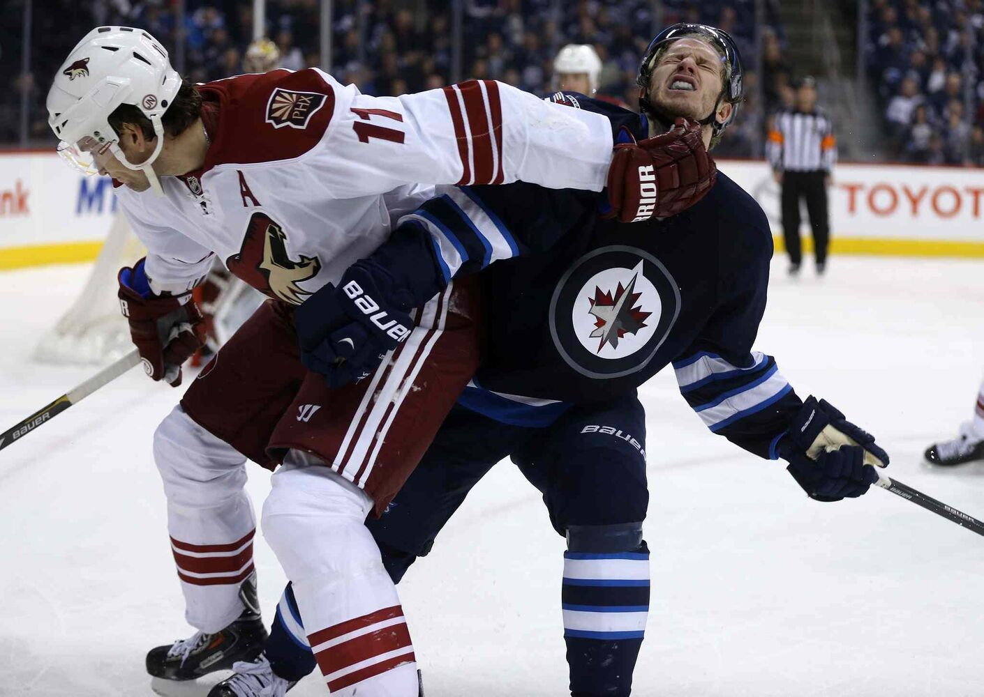 Coyotes Martin Hanzal (left) gives Winnipeg Jets' Bryan Little a forearm to the face. (Trevor Hagan / The Canadian Press)