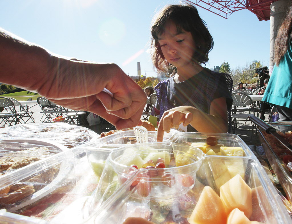 A girl picks her favourite fruit as a volunteer serves her during a KidBridge Thanksgiving feast. (John Woods / Winnipeg Free Press)