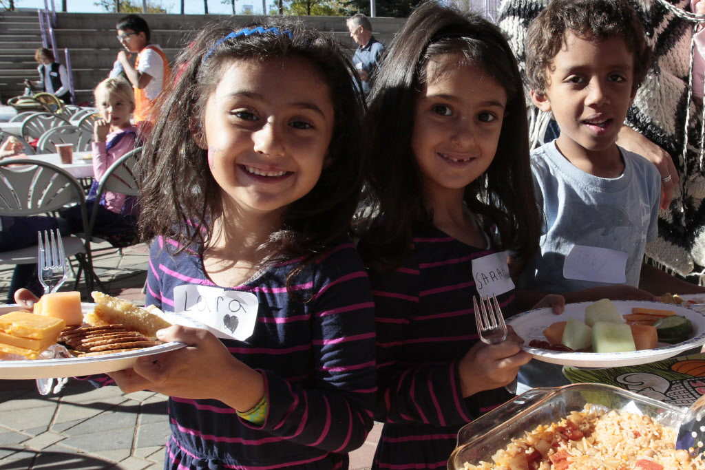 Larah and her sister Sarah Diab and their friend are served by volunteers during a KidBridge Thanksgiving feast.  (John Woods / Winnipeg Free Press)