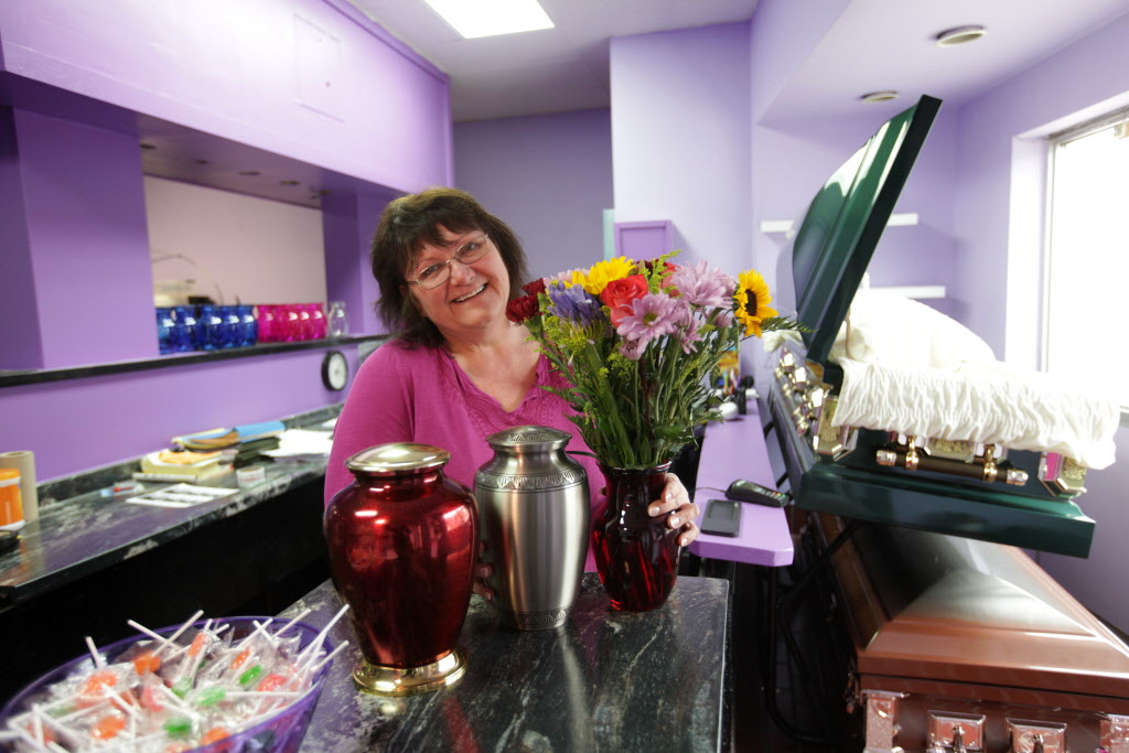 At a one-stop funeral shop, Leslie Borys displays products sold at a new Winnipeg storefront, which includes coffins and urns sold online, along with fresh-cut flowers in the former Kelekis restaurant.