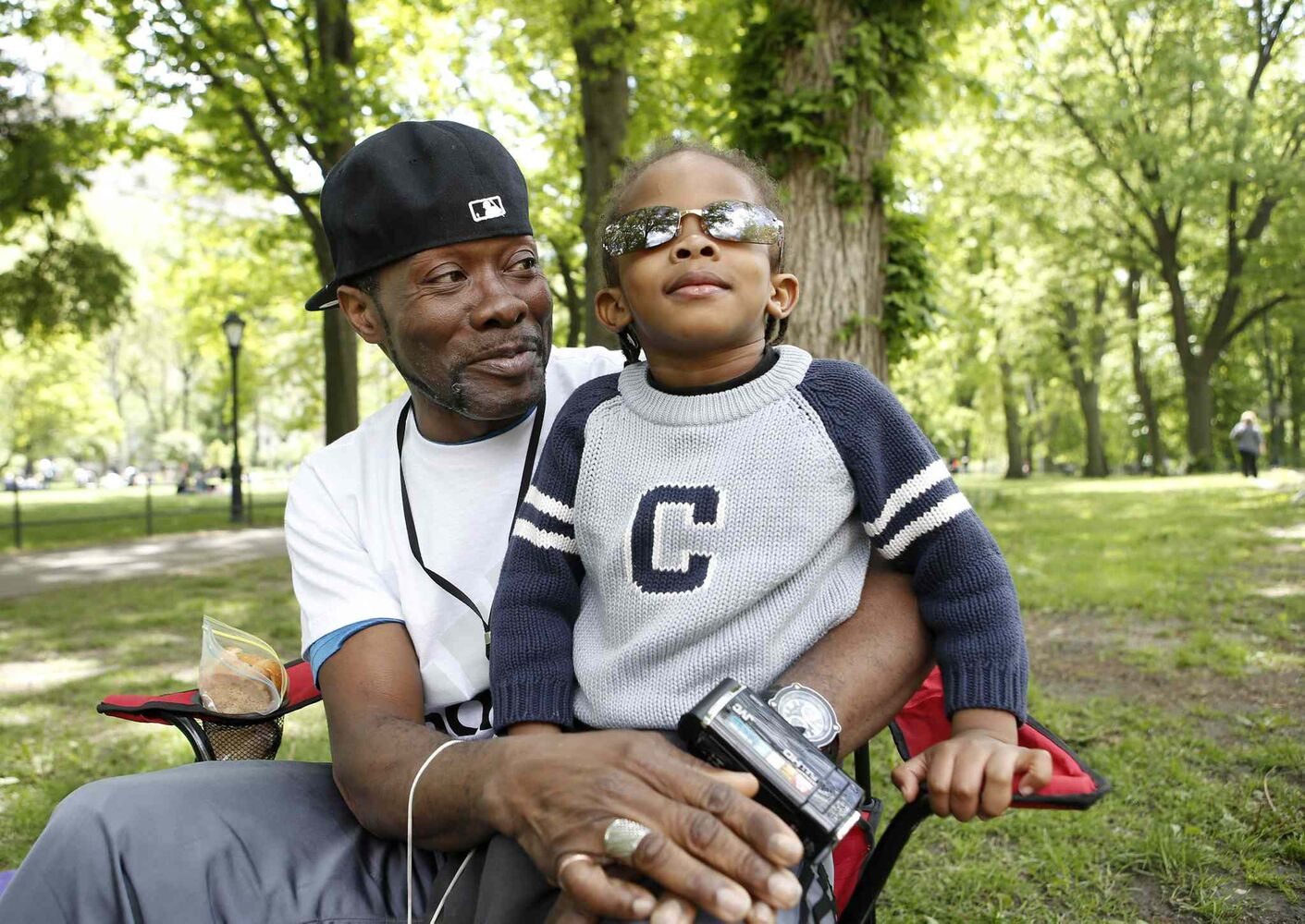 "Jamez James, 47, of the Brooklyn borough of New York, holds his son, Melchi-Tzdec, during an outing in New York's Central Park. Before becoming a father, James said, ""I was a single guy, living the life, well, so I thought."" James describes fatherhood as opening a door, and ""little did I know, as I chose to go through, my entire life changed... That's where I met my son, on the other side of the door.""  (Kathy Willens / The Associated Press)"