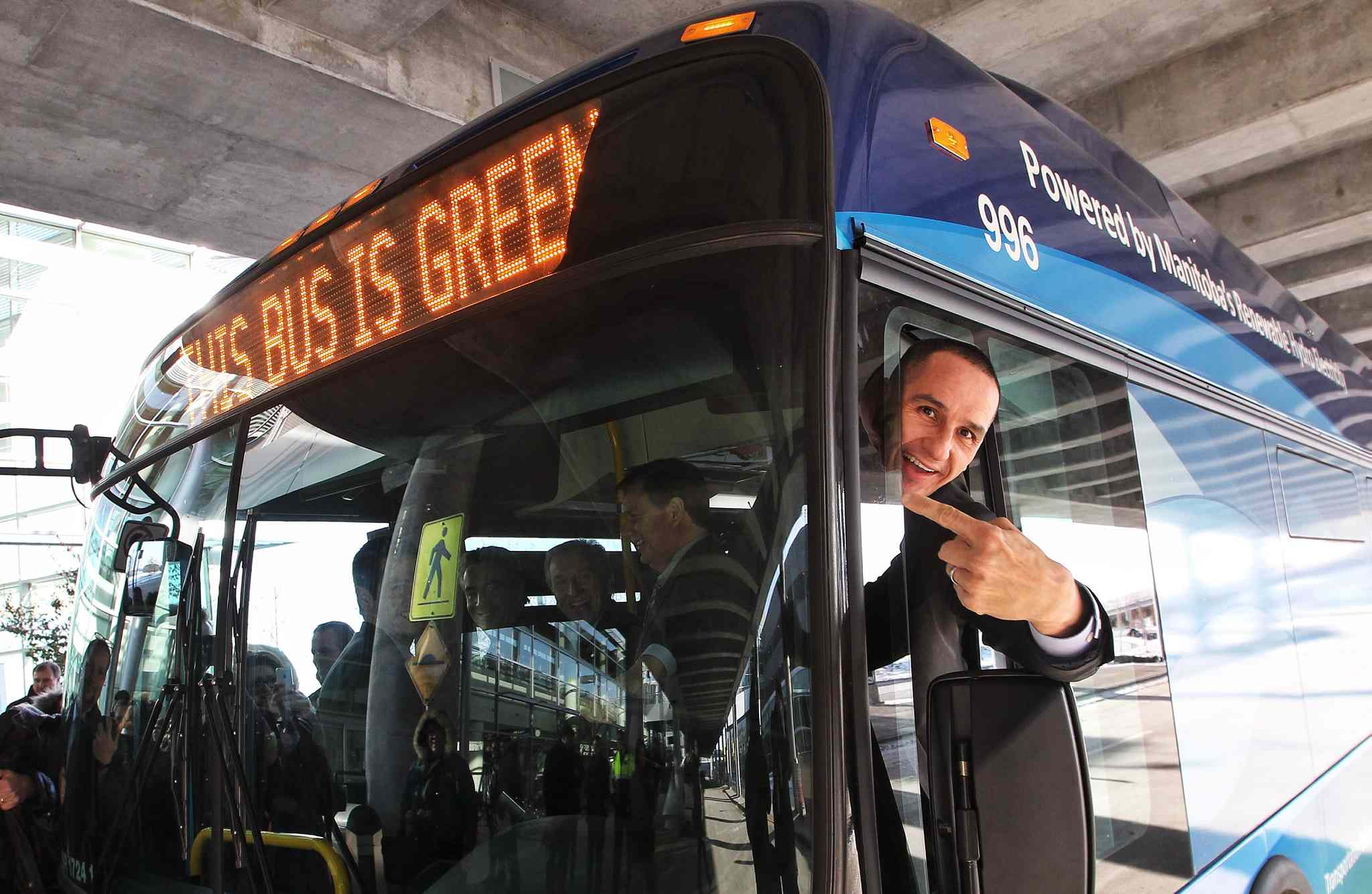 NDP Minister of Jobs and Industry, Kevin Chief, points to the sign stating the bus is environmentally friendly after the announcement that battery electric transit buses are going to be deployed at the James Richardson Armstrong Airport for Winnipeg Transit.