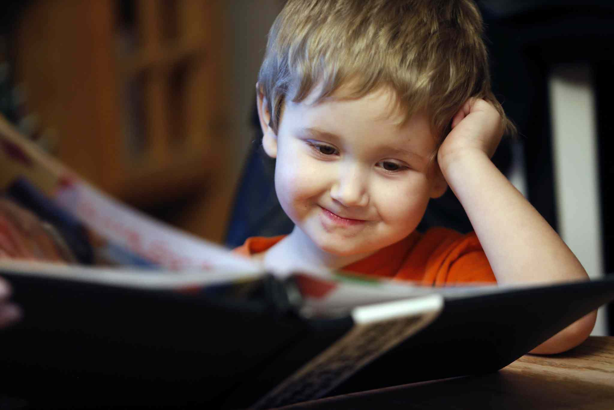 Benji, 4, looks at a photo album. He and his brother Hunter and sister Katie were adopted by Kelly and Mel Loeppky. The kids were in their fourth foster placement when they met the Loeppkys.