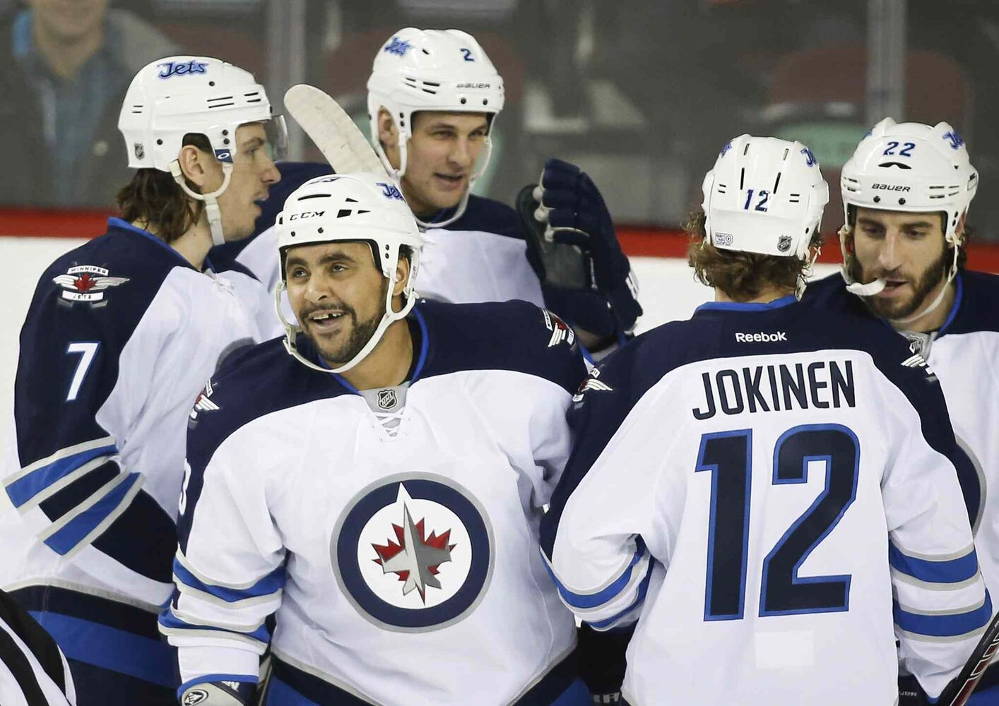 Winnipeg Jets' Dustin Byfuglien, second from left, celebrates his goal with teammates during the first period against the Calgary Flames in Calgary.