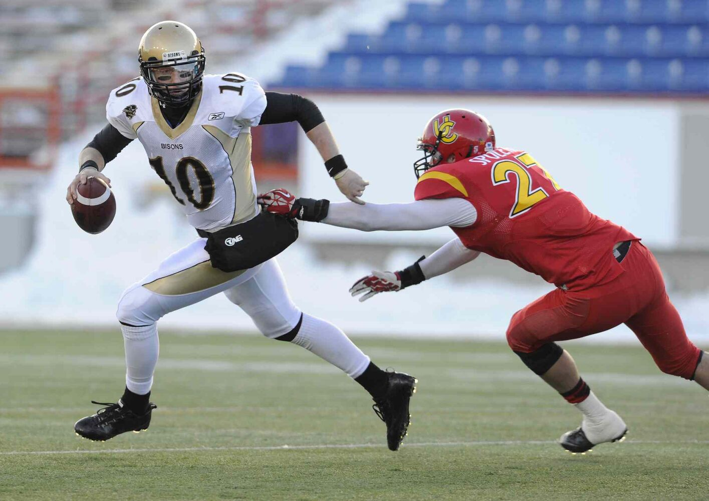 Manitoba Bisons quarterback Jordan Yantz (left) breaks away from Thomas Spoletini  of the Dinos during the first half.