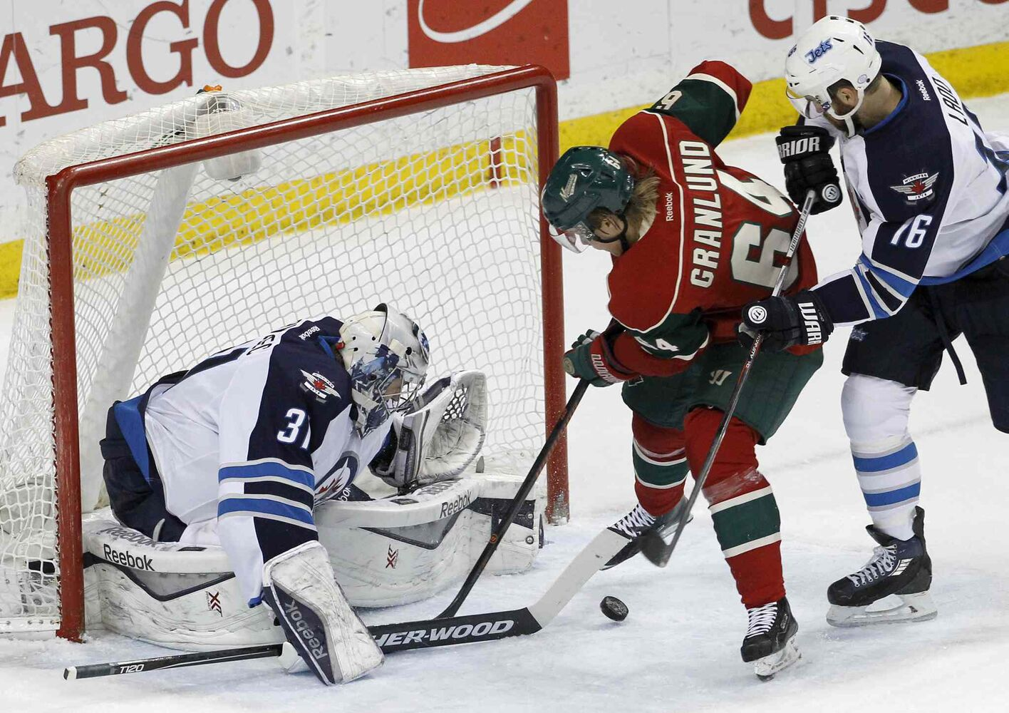 Winnipeg Jets goalie Ondrej Pavelec (31) deflects a shot by Minnesota Wild centre Mikael Granlund (64) as Jets left wing Andrew Ladd, right, defends during the first period of Monday's game. (Ann Heisenfelt / The Associated Press )