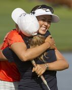 Cristie Kerr, left, gives Michelle Wie a hug celebrating Wie's win at the 2014 LPGA LOTTE Championship golf tournament at Ko Olina Golf Club, Saturday, April 19, 2014, in Kapolei, Hawaii. (AP Photo/Eugene Tanner)
