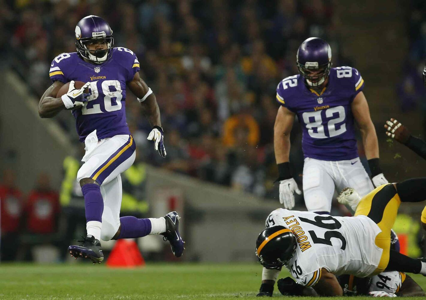 Minnesota Vikings running back Adrian Peterson (left) blasts past Pittsburgh Steelers linebacker LaMarr Woodley to score a 70-yard touchdown during the Vikes' 34-27 win at Wembley Stadium, London, on Sunday. (matt dunham / the associated press)