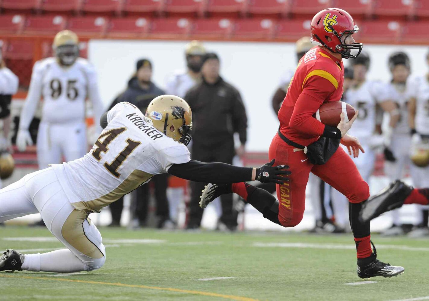 University of Calgary Dinos quarterback Andrew Buckley (right) breaks away from Lauren Kroeker of the University of Manitoba Bisons during the first half of Hardy Cup CIS football action in Calgary Saturday. (Larry MacDougal / The Canadian Press)