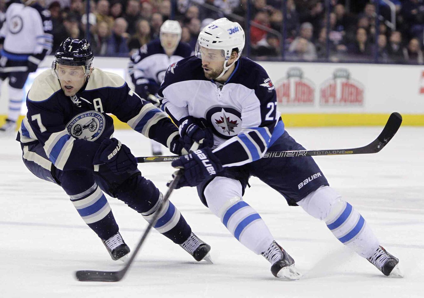 Winnipeg Jets' Eric Tangradi (right) carries the puck across the blue line as Columbus Blue Jackets' Jack Johnson defends during the first period Monday. (Jay LaPrete / The Associated Press)