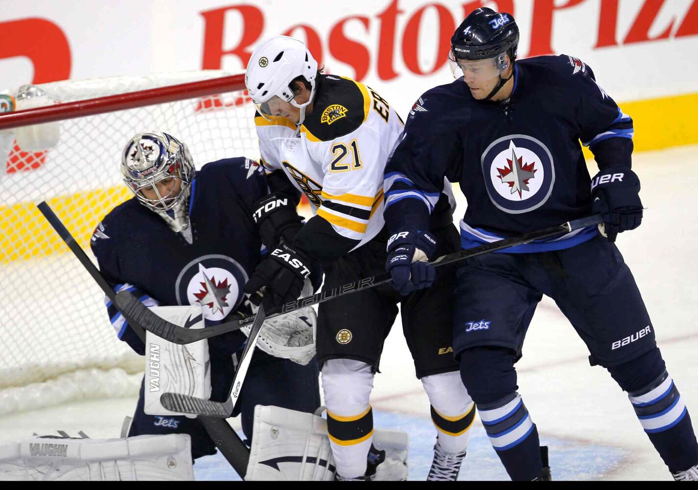 Loui Eriksson of the Boston Bruins and Paul Postma of the Winnipeg Jets jostle in front of Ondrej Pavelec in the first period.