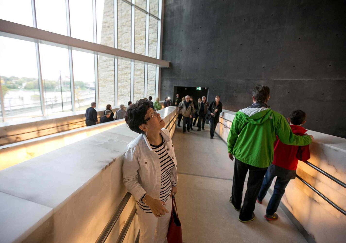 Teresa Yong, who travelled from British Columbia, glances up at the dozens of alabaster ramps stacked throughout the Canadian Museum for Human Rights. Thousands had reserved tickets for the four gallery preview tour on Saturday and Sunday. That is only four of 11 galleries, the rest of which open Sept. 27. (Melissa Tait / Winnipeg Free Press)