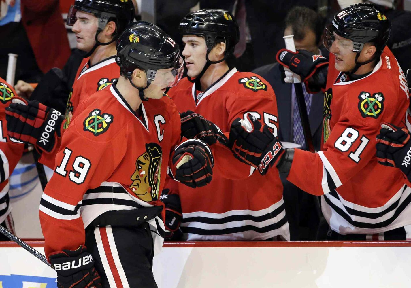 Chicago Blackhawks' Jonathan Toews (19) celebrates with teammates after scoring a goal during the first period.
