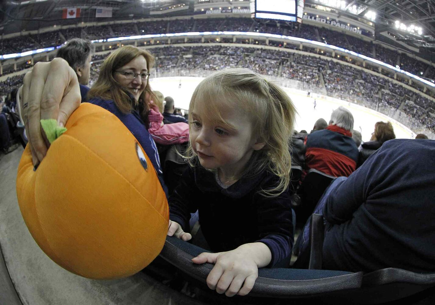 Gary and Kelly Depaulo brought their granddaughter, 21-month-old Jory Depaulo, to her first NHL hockey game. Kelly had to use other means to keep Jory entertained late in the third period as the Winnipeg Jets lost to the Columbus Blue Jackets at MTS Centre in Winnipeg Saturday. (Trevor Hagan / Winnipeg Free Press)