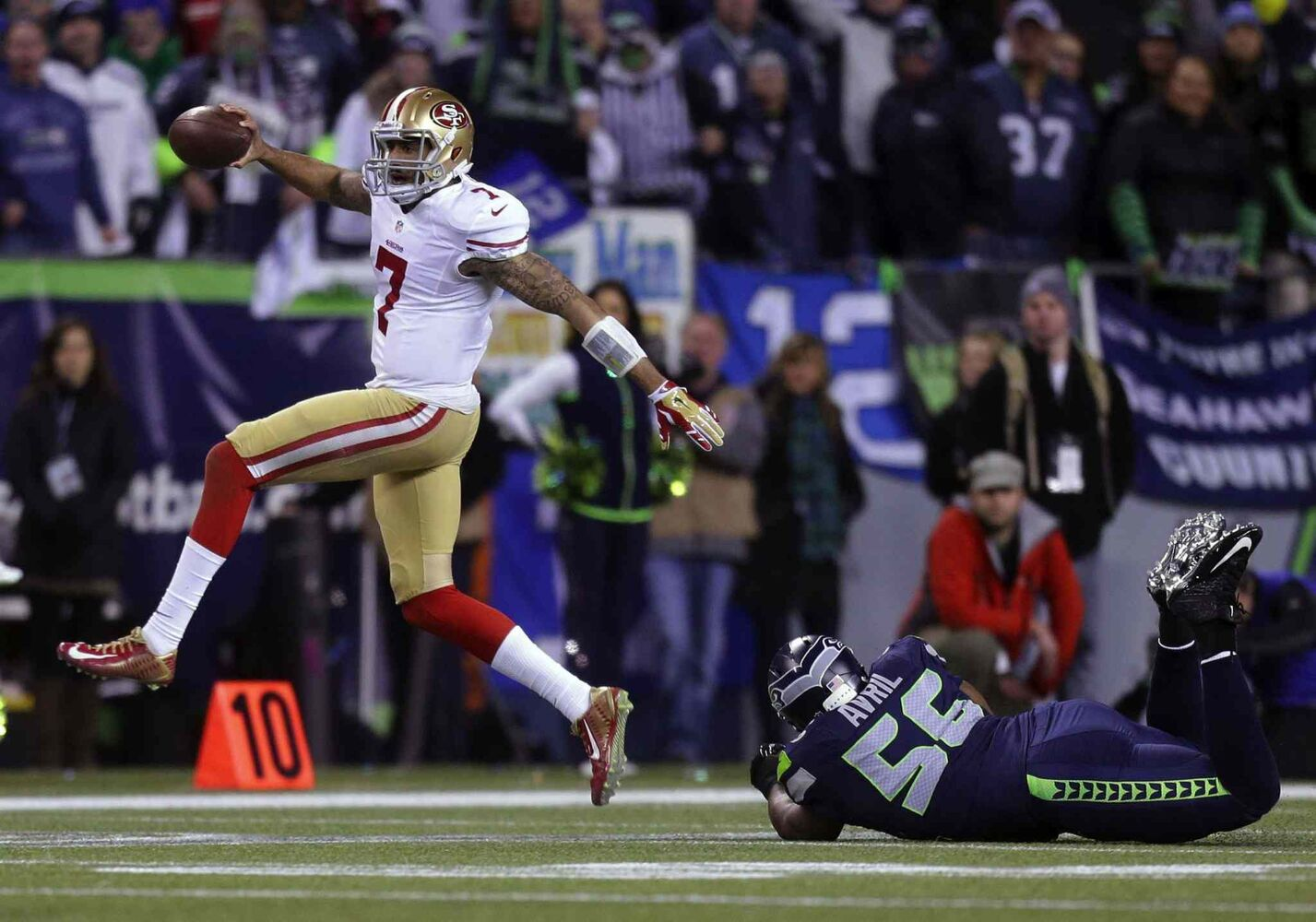 49ers QB Colin Kaepernick evades Seahawks defensive end Cliff Avril.   (Bettina Hansen / Tribune Media MCT)