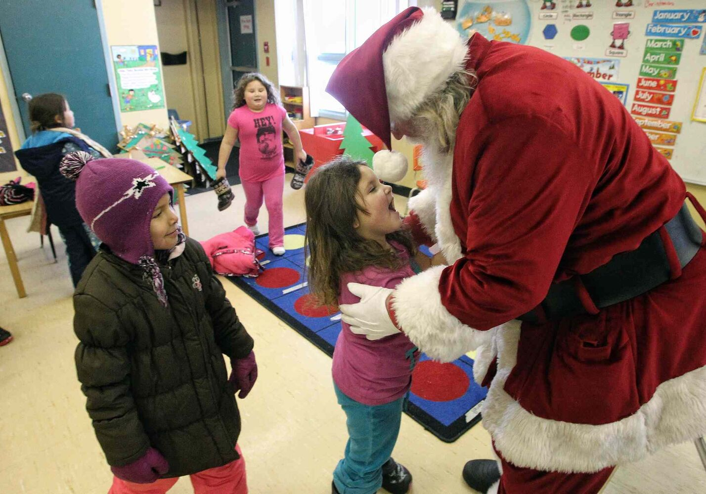 Madyson Bruneau, 6, gives Santa a hug as the jolly old elf meets kindergarten and Grade 1 kids on Wednesday during the Santa Express tour at Sergeant Tommy Prince School on the Brokenhead Ojibway First Nation.