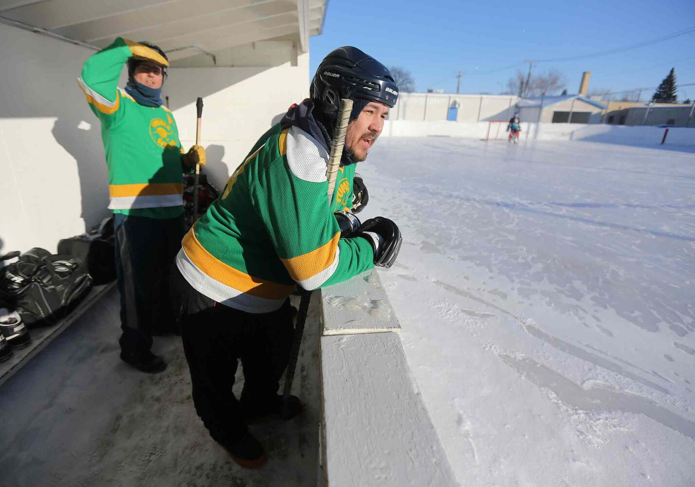 Tom McMahon, left, and Dewey Ackegan watch from the bench as their teammates battle it out against the Mighty Puckin' Drunks. (Trevor Hagan / Winnipeg Free Press)