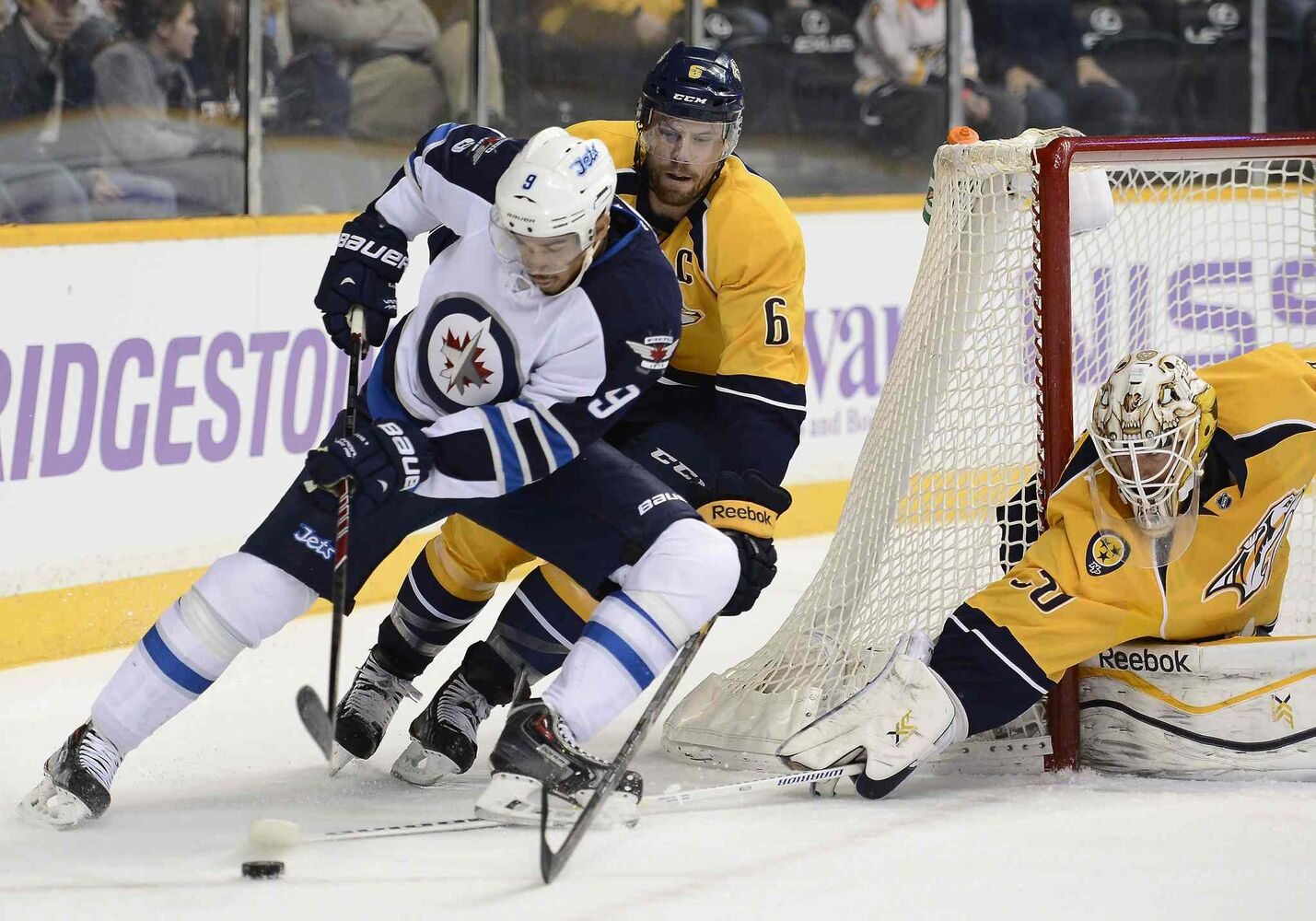 Winnipeg Jets' left wing Evander Kane (9) brings the puck around the net as he is defended by Nashville Predators defenseman Shea Weber (6) and goalie Carter Hutton (30) during the first period of Saturday's game.