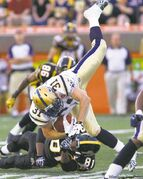 Blue Bombers safety Ian Logan is upended by Hamilton's Aaron Kelly after making a second-half interception.
